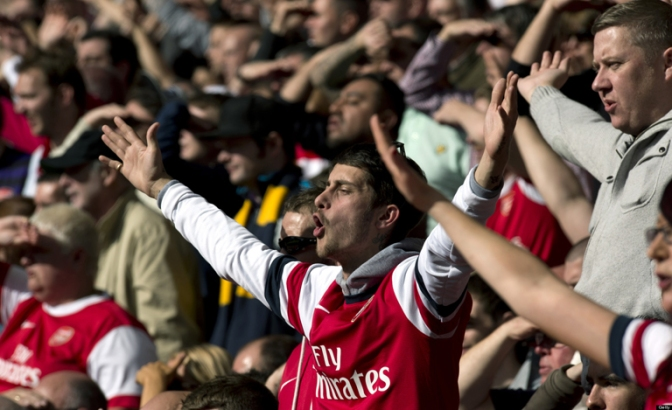 An Arsenal supporter sings in the crowd during the English Premier League football match between Arsenal and Chelsea at The Emirates Stadium in north London, England on September 29, 2012. AFP PHOTO/ADRIAN DENNIS RESTRICTED TO EDITORIAL USE. No use with unauthorized audio, video, data, fixture lists, club/league logos or ?live? services. Online in-match use limited to 45 images, no video emulation. No use in betting, games or single club/league/player publications.        (Photo credit should read ADRIAN DENNIS/AFP/GettyImages)