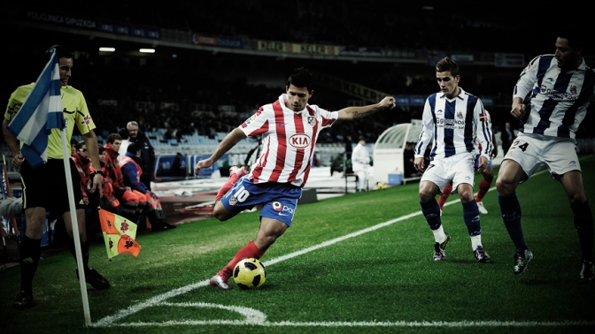 Atletico de Madrid's Sergio Leonel 'Kun' Aguero from Argentina, front, tries to kicks the ball  in front of Real Sociedad's  Alberto de la Bella, right, and Antoine Griezmann from France, center, during their Spanish La Liga soccer match at Anoeta stadium in San Sebastian northern,  Spain Sunday, Nov.21,  2010. (AP Photo/Alvaro Barrientos)