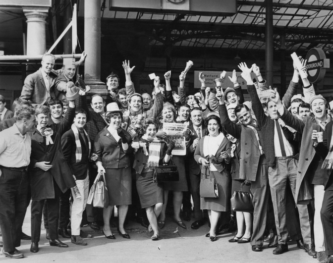Liverpool fans at Euston Station, London, 1st May 1965. They are on their way to see their team play Leeds United in the FA Cup final at Wembley. A woman (centre) is holding a copy of the Evening Standard newspaper with the headline 'Liverpool trying for cup double'. Liverpool later won the final 2-1. (Photo by Central Press/Hulton Archive/Getty Images)