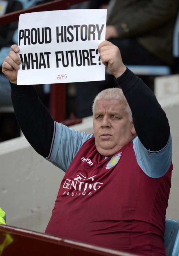 An Aston Villa fan holds a sign questioning his teams performances during the English Premier League football match between Aston Villa and Chelsea at Villa Park in Birmingham, central England on April 2, 2016. / AFP PHOTO / OLI SCARFF / RESTRICTED TO EDITORIAL USE. No use with unauthorized audio, video, data, fixture lists, club/league logos or 'live' services. Online in-match use limited to 75 images, no video emulation. No use in betting, games or single club/league/player publications. / OLI SCARFF/AFP/Getty Images
