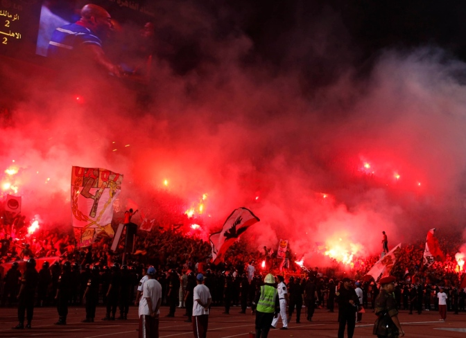 Fans wave flags and light flares as police in riot gear stand guard during the Egyptian Premier League soccer match between Al-Ahly and Zamalek in Cairo June 29, 2011. REUTERS/Mohamed Abd El-Ghany (EGYPT - Tags: SPORT SOCCER)